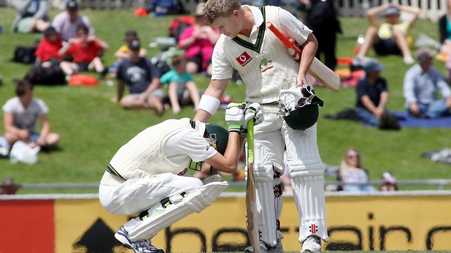 David Warner consoles a disconsolate Nathan Lyon after their valiant last wicket partnership fell just seven runs short in Hobart